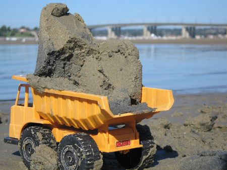 Yellow toy dump truck in the sand carrying a load with view of beach and bridge   photo