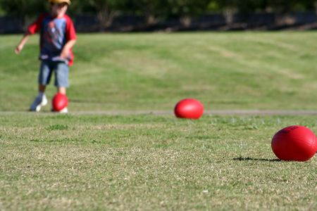 afl: Boy kicking a rugby ball with two others on the field
