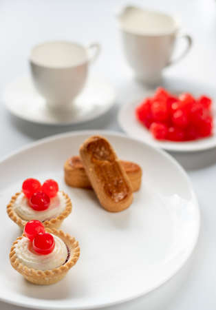 Dessert of sweet chrries with almond fingers and two basket cakes and coffe cup and milk jug at the background