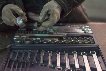 workshop worker choosing the right wrench from wrench set