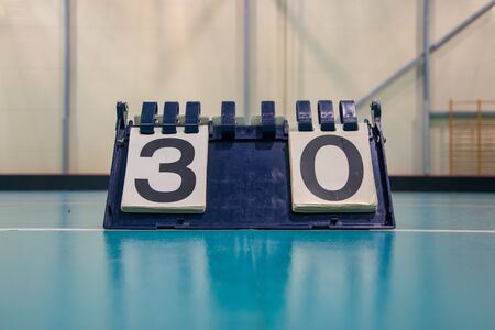 Score board inside the gym on the floor shows result 3:0