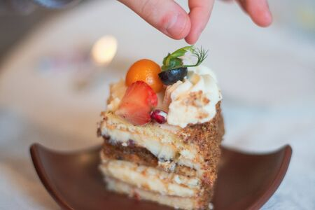 Fingers are reaching for peace of cake on brown plate