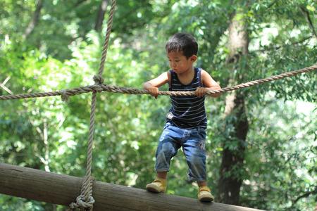 日本の少年が綱渡りで遊んで 写真素材