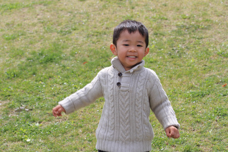 Japanese boy running on the grass