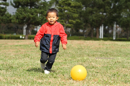 Japanese boy kicking a yellow ball Stock Photo