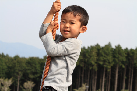 tarzan: Japanese boy playing with tarzan rope Stock Photo