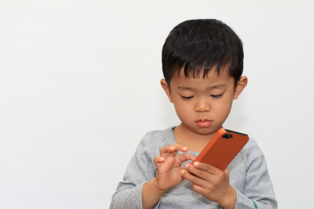 Japanese boy using smart phone photo