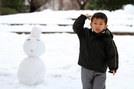 Japanese boy having snowball fight and snowman photo