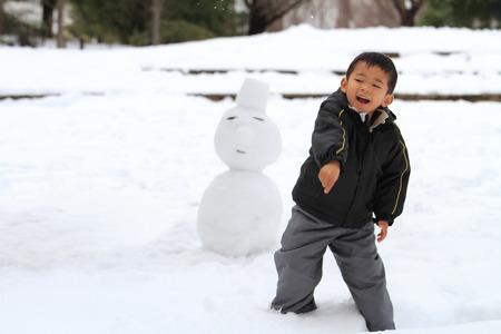 雪玉の戦いと雪だるまを持つ日本の少年
