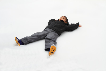 Japanese boy lying on the snow field photo