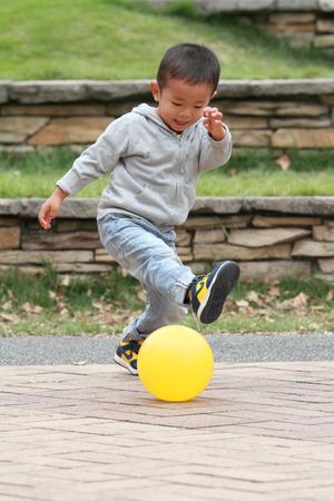 日本男児 (3 歳) 黄色のボールを蹴る