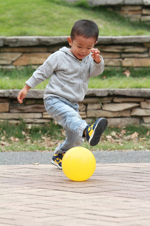 soccer ball on grass: Japanese boy kicking a yellow ball (3 years old)