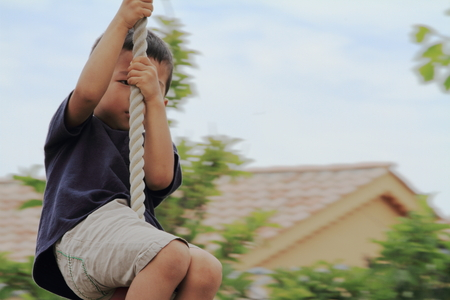 tarzan: Japanese boy playing with Tarzan rope (4 years old) Editorial