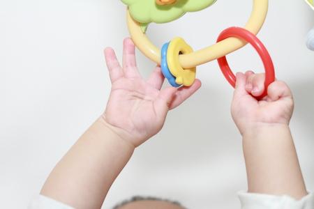 日本の赤ちゃんの女の子 0 歳おもちゃに彼女の手を伸ばす