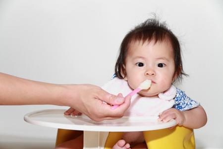 日本の赤ちゃんの離乳食 (0 歳) を食べる女子高生 写真素材