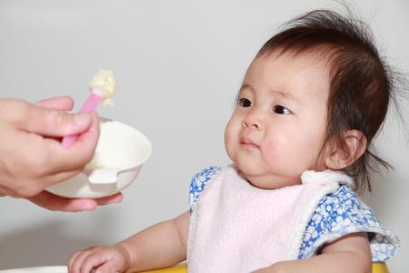 Japanese baby girl eating baby food (0 year old) 写真素材