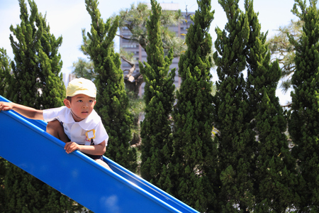 5 10 years old: Japanese boy on the slide (5 years old) Stock Photo