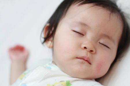 眠っている女の日本の赤ちゃん (0 歳)