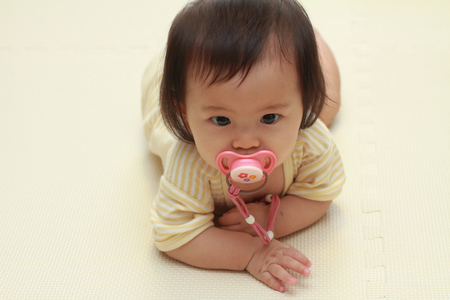 teether: Japanese baby girl sucking on a pacifier (0 year old)