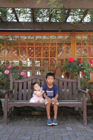 日本の兄と妹 (5 歳の男の子と 0 歳の女の子) のベンチに座って