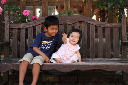 0 to 5: Japanese brother and sister (5 years old boy and 0 year old girl) sitting on the bench