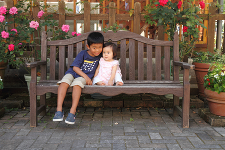5 0: Japanese brother and sister (5 years old boy and 0 year old girl) sitting on the bench