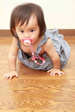 one female: Japanese baby girl sucking on a pacifier (0 year old)