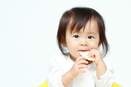 baby rice: Japanese baby girl eating rice cracker (0 year old)