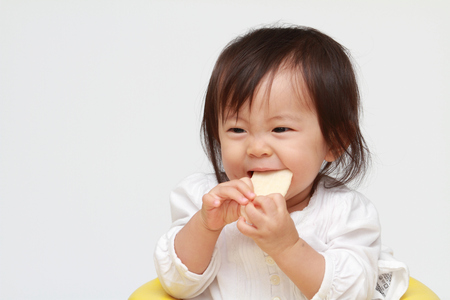 Japanese baby girl eating rice cracker (0 year old)