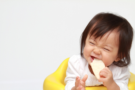 baby rice: Japanese baby girl eating rice cracker (0 year old)