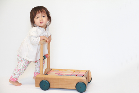 niños caminando: niña japonesa que empuja un carro (1 año de edad) Foto de archivo