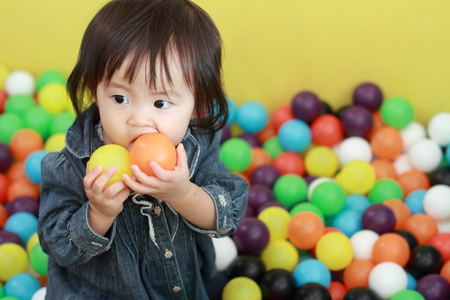 Japanese baby girl playing in ball pool (1 year old)