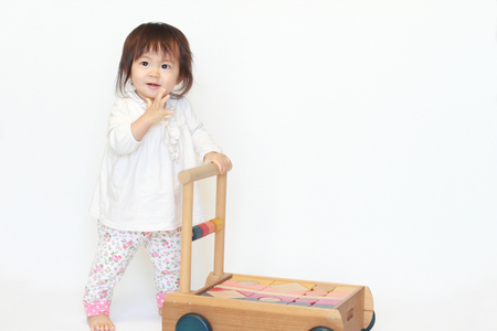 日本の赤ちゃんの女の子 (1 歳) カートを押して