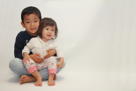 6 year old: Japanese brother and sister sitting on his knee (6 years old boy and 1 year old girl) Stock Photo