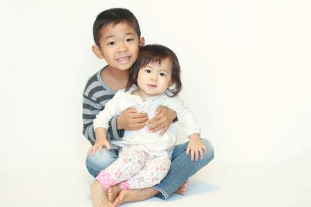 日本の兄と妹 (6 歳の男の子と 1 歳の女の子) 彼の膝の上に座って