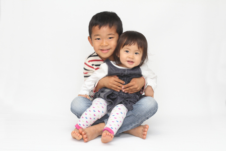 asian baby girl: Japanese brother and sister sitting on his knee (6 years old boy and 1 year old girl) Stock Photo