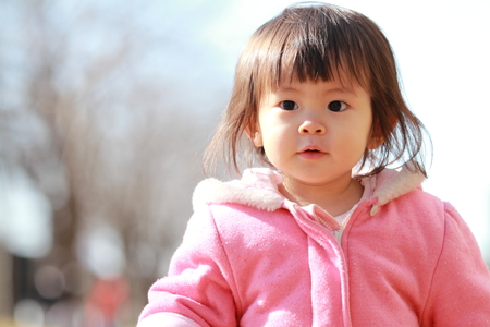 winter weather: Smiling Japanese baby girl under the blue sky (1 year old) Stock Photo