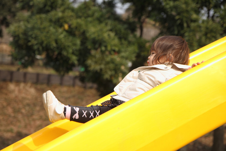 play the old park: Japanese baby girl on the slide (1 year old) Stock Photo