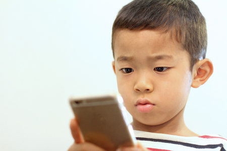6 years: Japanese boy using a smart phone (6 years old) Stock Photo