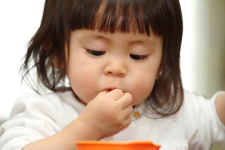 日本の赤ちゃんの女の子 (1 歳) 穀物を食べて
