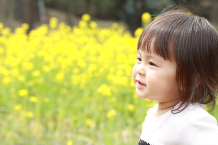 mustard field: Japanese baby girl (1 year old) and yellow field mustard