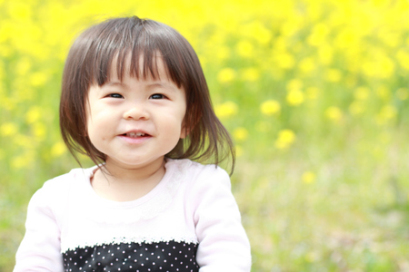 asian infant: Japanese baby girl (1 year old) and yellow field mustard