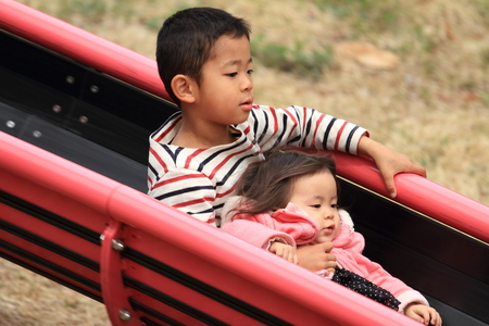 6 year old: Japanese brother and sister on the slide (6 years old boy and 1 year old girl) Stock Photo