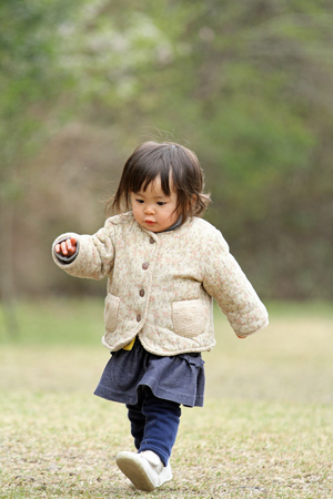 one year: Japanese girl walking on the grass (1 year old)