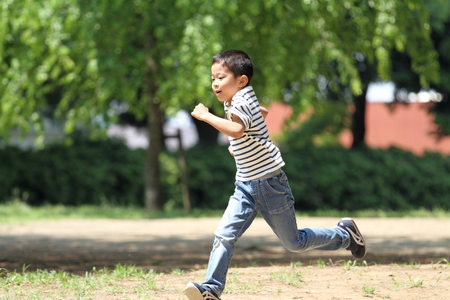 Japanese boy running on the grass?(first grade at elementary school)
