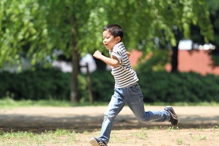 Japanese boy running on the grass?(first grade at elementary school)