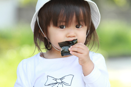 baby rice: Japanese girl eating rice ball (1 year old)