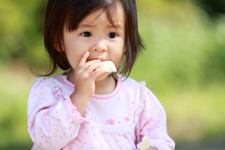 baby rice: Japanese girl eating rice cracker (1 year old)