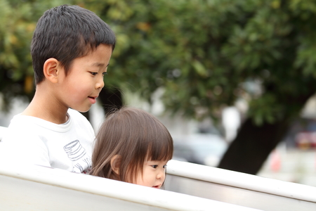 6 years: Japanese brother and sister on the slide (6 years old boy and 1 year old girl) Stock Photo