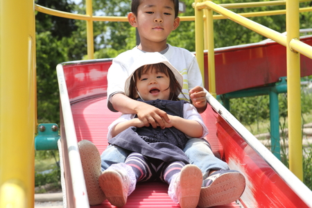 first year student: Japanese brother and sister on the slide (6 years old boy and 1 year old girl) Stock Photo